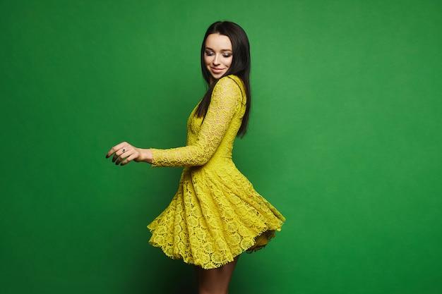 Brunette model meisje met lichte make-up in korte stijlvolle gele jurk ronddraaien Premium Foto