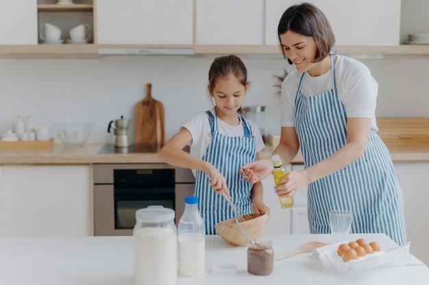 Brunette moeder voegt olie toe aan deeg, dochtertje helpt om gebak te maken, klopt ingrediënten Premium Foto