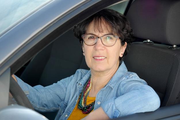 Brunette volwassen vrouw rijdende auto Premium Foto