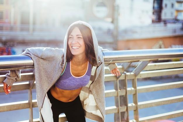 Brunette vrouw draagt sportkleding lachend Gratis Foto