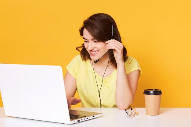 Brunette vrouw in gele casual t-shirt zit op stoel aan witte bureau en werkt op laptop op, heeft een aangenaam gesprek met de klant, houdt de hand op garnituur, werkt online. Premium Foto