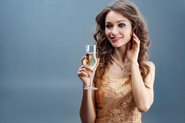 Brunette vrouw in gouden jurk en parelketting met verhoogd glas champagne en raak zelf gezicht voor de hand Premium Foto