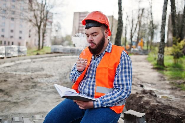 Brutale baard rokende werknemer man pak bouwvakker in oranje veiligheidshelm zittend op de stoep, pauze op het werk, en lees werken notebook ingangen. Premium Foto
