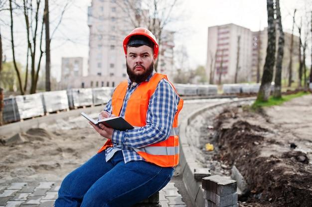 Brutale baard werknemer man pak bouwvakker in oranje veiligheidshelm zittend op de stoep en maakt werken notebook ingangen. Premium Foto