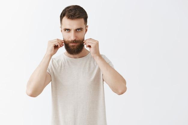 Brutale bebaarde bebaarde man die zich voordeed tegen de witte muur Gratis Foto