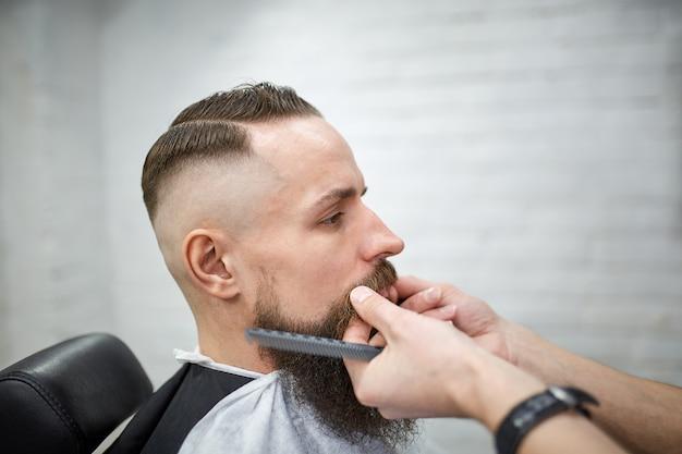 Brutale kerel in moderne kapperszaak. kapper maakt kapsel een man met een lange baard. hoofdkapper doet kapsel door schaar en kam Premium Foto