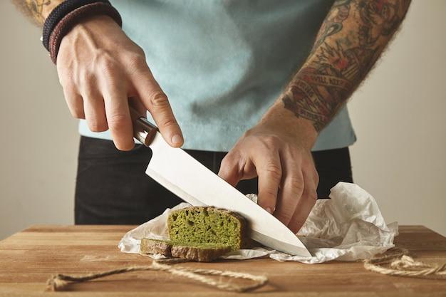 Brutale man getatoeëerde handen gesneden gezonde spinazie zelfgemaakte groene rustieke brood met vintage mes op plakjes. houten plank witte tafel Gratis Foto