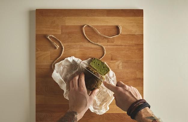 Brutale man getatoeëerde handen gesneden gezonde spinazie zelfgemaakte groene rustieke brood met vintage mes op plakjes. houten plank witte tafelblad weergave Gratis Foto