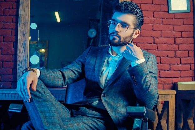 Brutale man in elegant pak en glazen in herenkapper Premium Foto