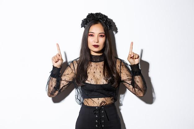 Brutale mooie aziatische vrouw in zwarte gotische jurk, heksenkostuum dragen voor halloween en vingers omhoog wijzend, met je logo of banner op lege witte achtergrond, witte achtergrond. Gratis Foto