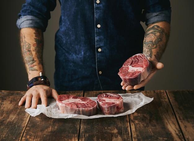 Brutale slager met getatoeëerde handen biedt een stuk geweldig rauw vlees biefstuk op camera, andere steaks in wit kraftpapier op vintage oude houten grunge tafel. onherkenbaar Gratis Foto