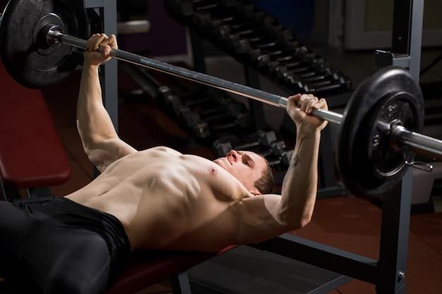 Brute atletische man oppompen van spieren op bankdrukken Premium Foto