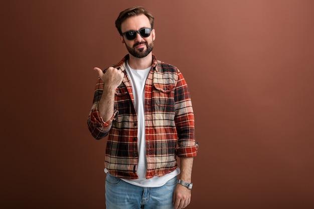 Brute hipster knappe stijlvolle bebaarde man op bruin Gratis Foto