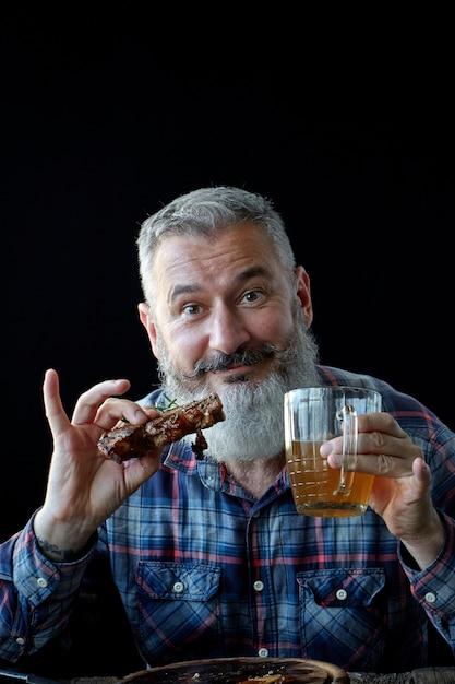 Brute volwassen man met grijs haar, gek op mosterdsteak en bier, vakantie, festival, oktoberfest of st. patrick's day Premium Foto