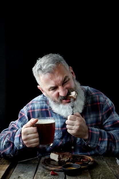 Brute volwassen man met grijs haar, gek op mosterdsteak en bier Premium Foto