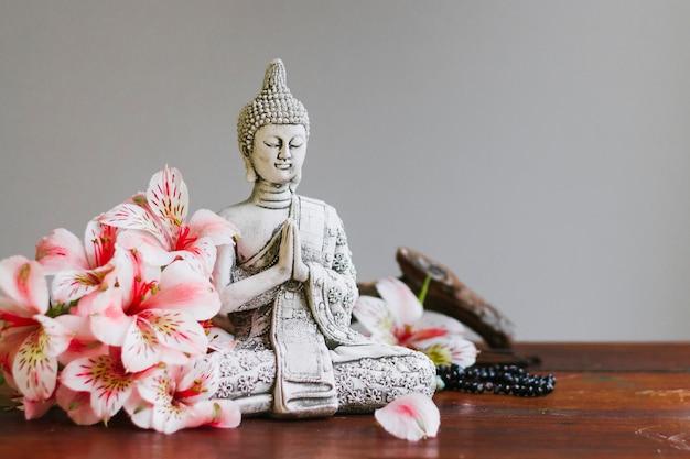 Buda-beeldhouwwerk met bloemblaadjes Gratis Foto