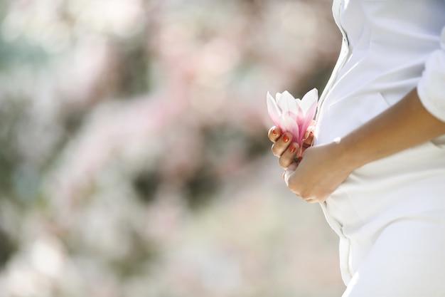 Buik van een zwangere vrouw en een bloem Gratis Foto
