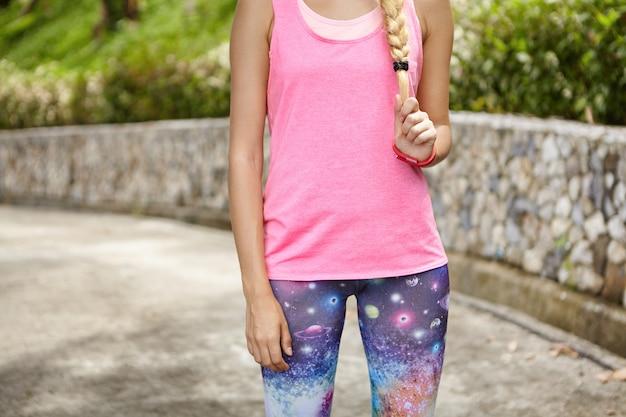 Buik van fit blonde sportvrouw gekleed in roze tank top en ruimte print legging rust buiten, trekken haar vlecht, staande in groen park. atletische meisje ontspannen tijdens de training Gratis Foto