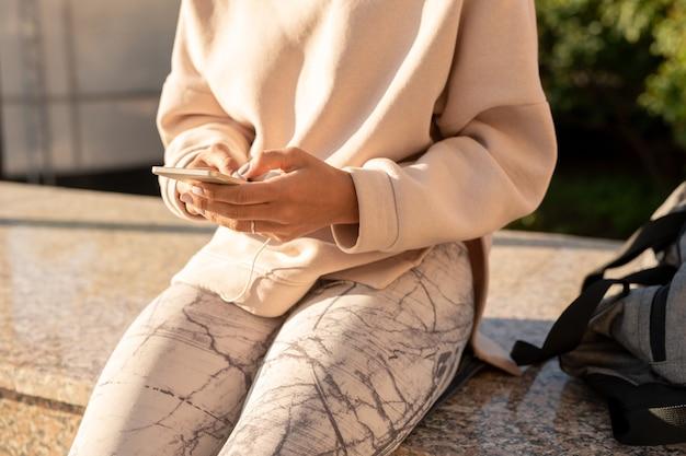 Buik van jonge hedendaagse vrouwelijke duizendjarige in hoodie en leggings zittend op marmeren tegels na buitentraining en met behulp van gadget Premium Foto