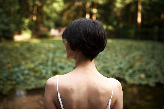 Buiten achteraanzicht van jonge brunette meisje met kort kapsel prachtige wilde natuur bewonderen Gratis Foto