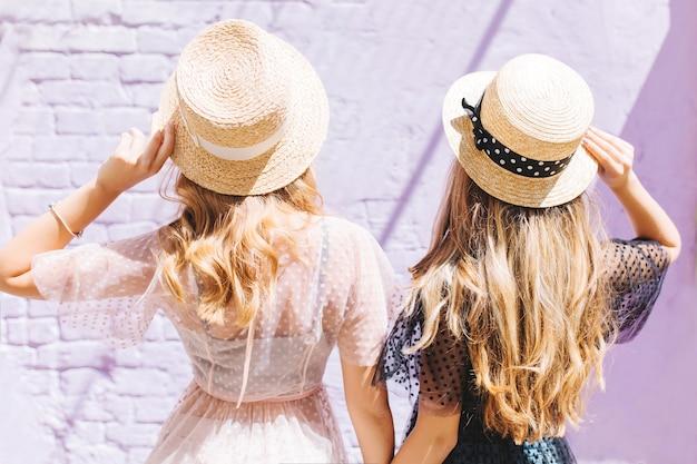 Buiten close-up portret van achterkant blonde krullende zusters tijd samen doorbrengen in zonnige ochtend Gratis Foto