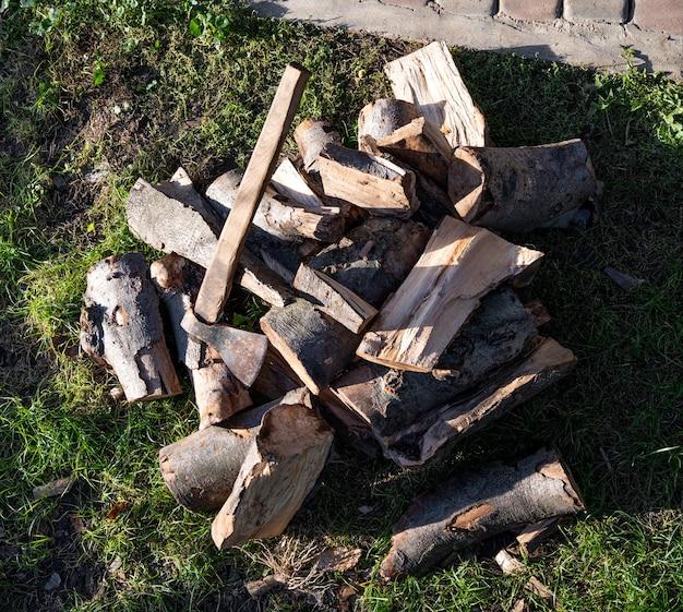 Buiten een bijl en een stapel gehakt hout Premium Foto