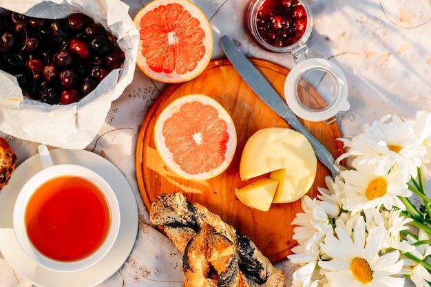 Buiten eten parkeren. fruit, croissants, jam, thee en bloemen op tafellaken in zonlicht. Premium Foto
