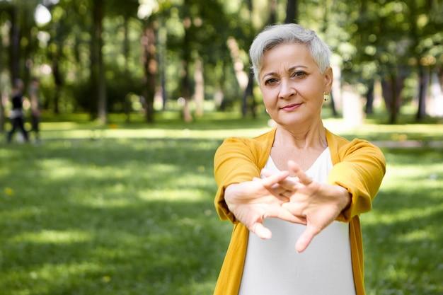 Buiten foto van aantrekkelijke grijze haren gepensioneerde vrouw haar armen spieren strekken, lichaam opwarmen voordat ochtend in park lopen. mensen, sport, gezond, fitness, veroudering, recreatie en activiteitenconcept Gratis Foto