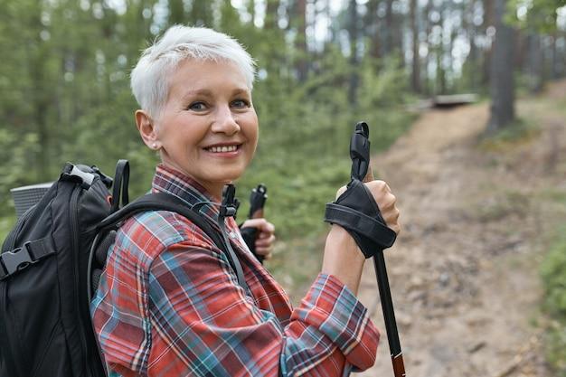 Buiten foto van mooie energieke volwassen vrouw met rugzak met behulp van stokken, genieten van nordic walking in het bos, camera kijken met een blije glimlach Gratis Foto