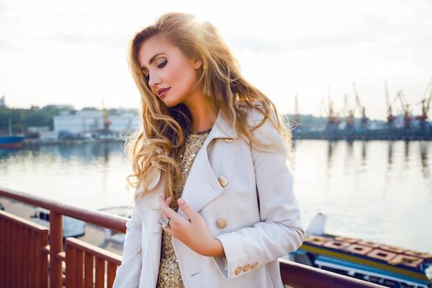 Buiten herfst mode portret van sexy elegante dame poseren nette zeehaven dromen en denken, het dragen van witte kasjmier witte jas hebben gekrulde haren en lichte make-up. avondzonlicht, zachte kleuren. Gratis Foto