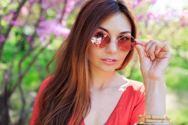 Buiten lente close-up portret van brunette vrouw genieten van bloemen in zonnige bloeiende tuin. Gratis Foto