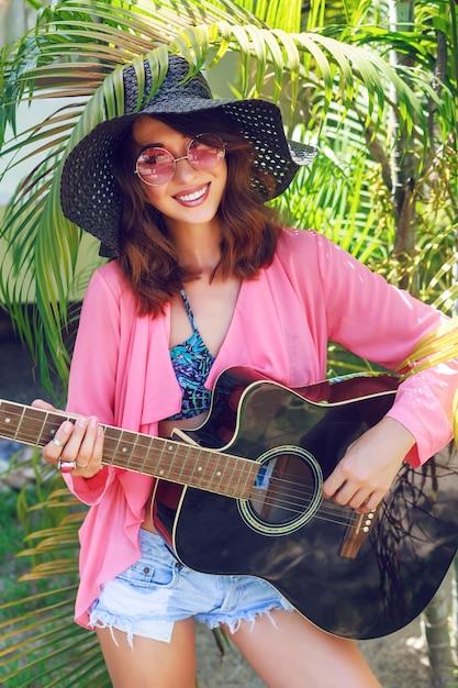 Buiten mode portret van gelukkig vrij lachende hippie vrouw zittend op het gras en akoestische gitaar te houden. heet tropisch land, groene achtergrond. zomeroutfit met hoed en roze zonnebril. Gratis Foto