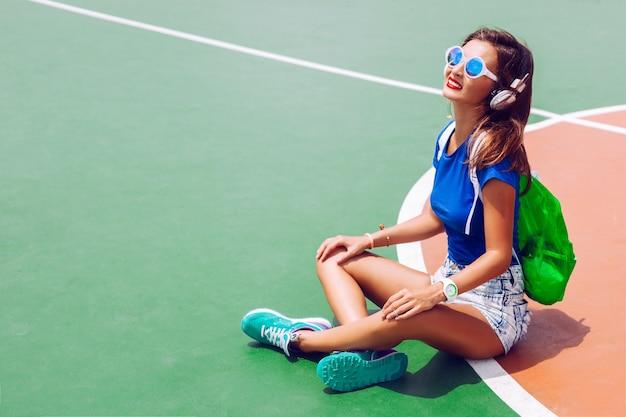 Buiten mode portret van hipster meisje poseren op sportveld in heldere zomer outfit, muziek luisteren en stijlvolle sportieve schoenen rugzak en zonnebril dragen. Gratis Foto