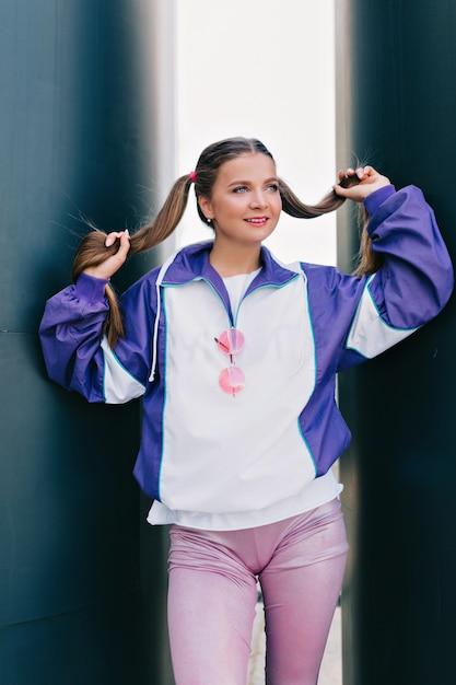 Buiten mode portret van jonge charmante vrouwelijke model helder jasje en roze broek met verzameld haar poseren met lichte glimlach dragen Gratis Foto