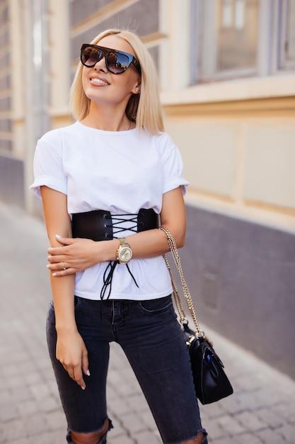 Buiten mode portret van jonge mooie blonde vrouw in zonnige dag op straat. meisje in zonnebril buiten. gelukkig mode vrouw in zonnebril. glimlachend trendy meisje in de zomer. Gratis Foto