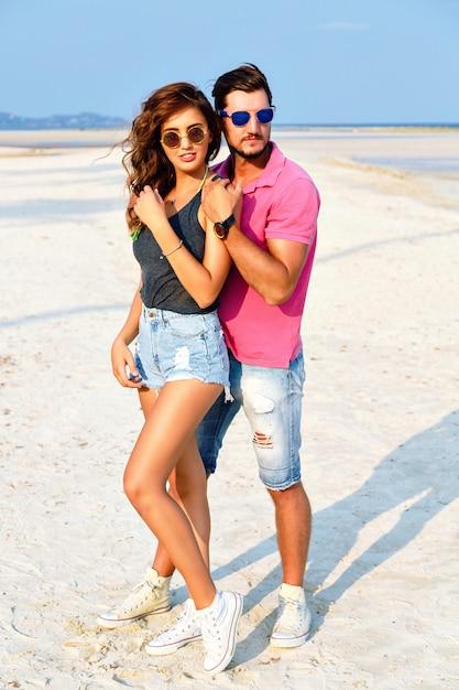 Buiten mode portret van jonge mooie paar verliefd poseren op geweldig strand, heldere stijlvolle casual kleding en zonnebril dragen, genieten van hun zomervakantie in de buurt van de oceaan. Gratis Foto