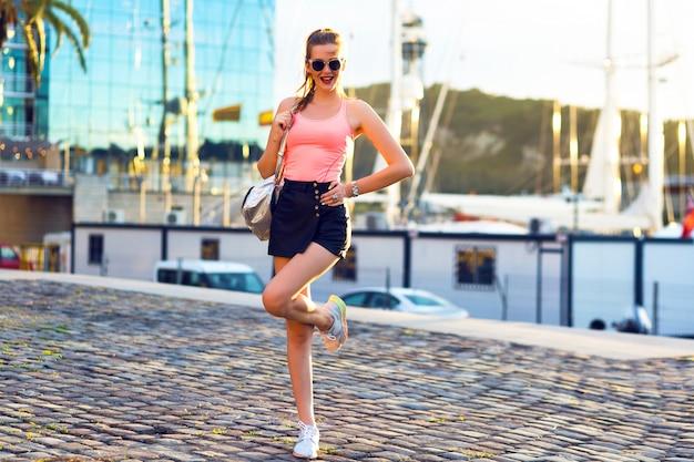 Buiten mode portret van jonge sportieve vrouw plezier reizen en wandelen bij luxe jachtclub, avondzonlicht, felle kleuren Gratis Foto