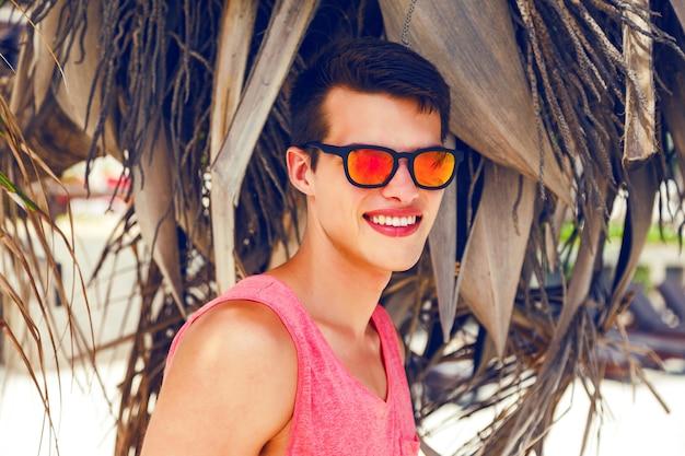 Buiten mode portret van knappe stijlvolle man geweldige tijd doorbrengen op tropisch strand, poseren in de buurt van kokospalm, heldere outfit en neon zonnebril dragen. Gratis Foto