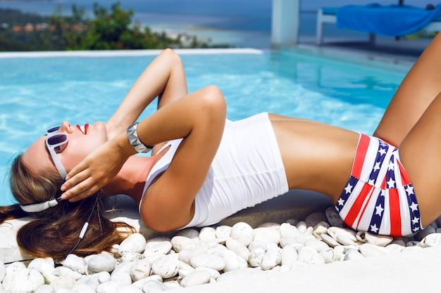 Buiten mode portret van prachtige vrouw met perfect lichaam, ontspannen bij het zwembad met prachtig uitzicht op de oceaan en het tropische eiland, geniet van de muziek op oortelefoons, sexy zomeroutfit dragen. Gratis Foto