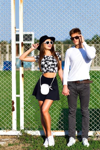 Buiten mode portret van verliefde paar knuffels op sportterrein, trendy zwart-witte kleding, vintage zonnebril, poseren op romantische date, zonnige dag, felle kleuren, liefde, relaties. Gratis Foto