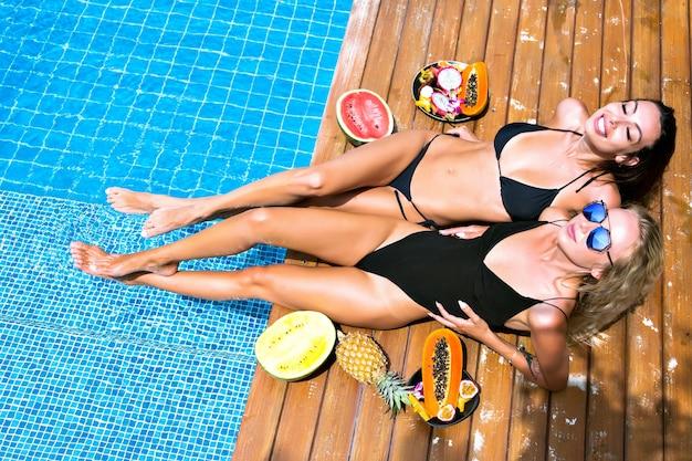 Buiten mode portret voor twee mooie vrienden meisjes met plezier leggen en ontspannen in de buurt van zwembadfeest, met zoete tropische vruchten, sexy bikini, zonnebril, gezelschapsplezier, zonnebaden. Gratis Foto