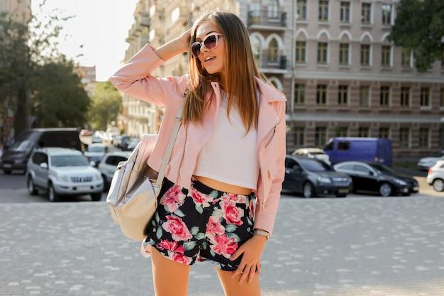 Buiten modieus portret van blonde vrouw die zich voordeed op straat. stijlvolle zonnebril, roze leren jas en rugzak dragen. Gratis Foto