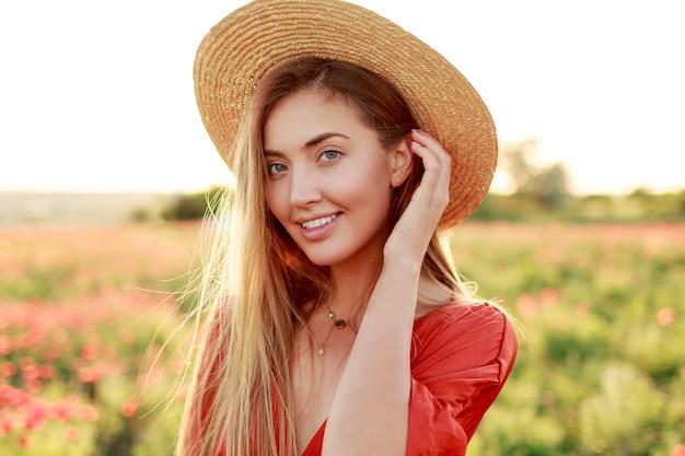 Buiten modieus portret van prachtige blonde vrouw poseren tijdens een wandeling in verbazingwekkende papaverveld in warme zomeravond. met strohoed, trendy tas en rode jurk. Gratis Foto
