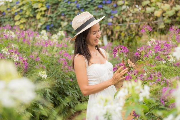 Buiten portret van een mooie vrouw van middelbare leeftijd azië. aantrekkelijk meisje in een veld met bloemen Gratis Foto