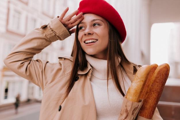 Buiten portret van jonge aantrekkelijke franse vrouw met lang lichtbruin haar, gekleed in rode baret Gratis Foto