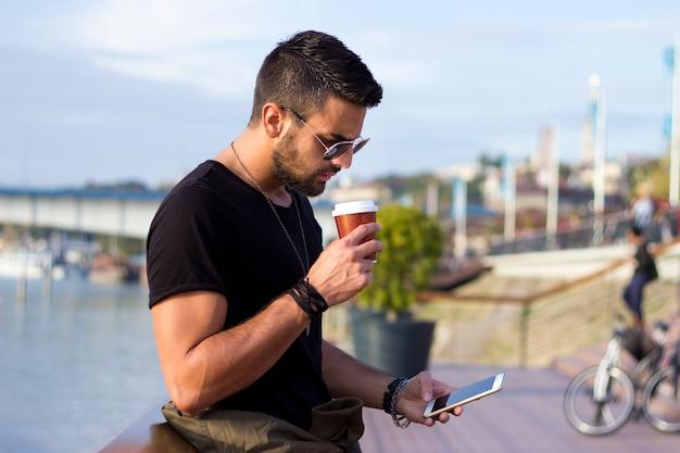 Buiten portret van moderne jonge man met mobiele telefoon in de straat met koffie. Gratis Foto