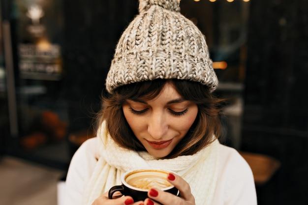 Buiten portret van vrij charmant meisje met koffie dragen in winter glb en witte trui in lichten. Gratis Foto