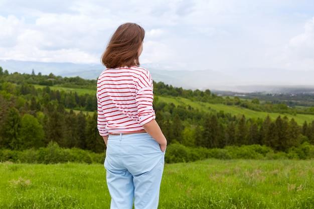 Buiten schot van aantrekkelijke jonge vrouw, gekleed in casual broeken en witte t-shirt met rode strepen Premium Foto