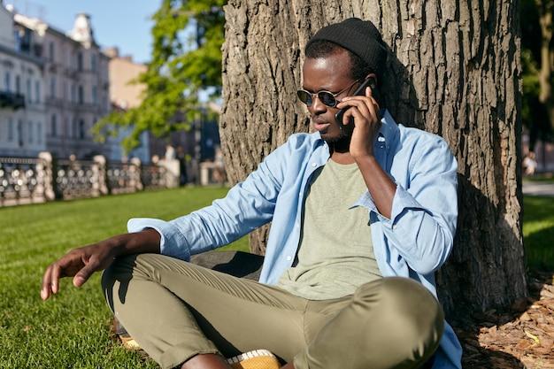 Buiten schot van donkere man in trendy bril, hoed, overhemd en broek, gekruiste benen zittend op groen gazon in de buurt van boom, zijn vrije tijd doorbrengen in het park, spreken via smartphone met vriend Gratis Foto