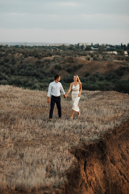 Buiten schot van een jong bruidspaar wandelen op de heuvel en hand in hand. Premium Foto